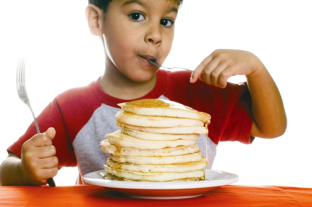 photo of child eating a giant stack of pancakes Summer Breakfast Program